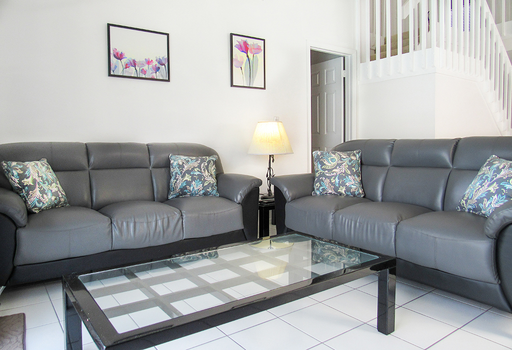 Family room, overlooking the pool from two directions and with comfortable leather couches.