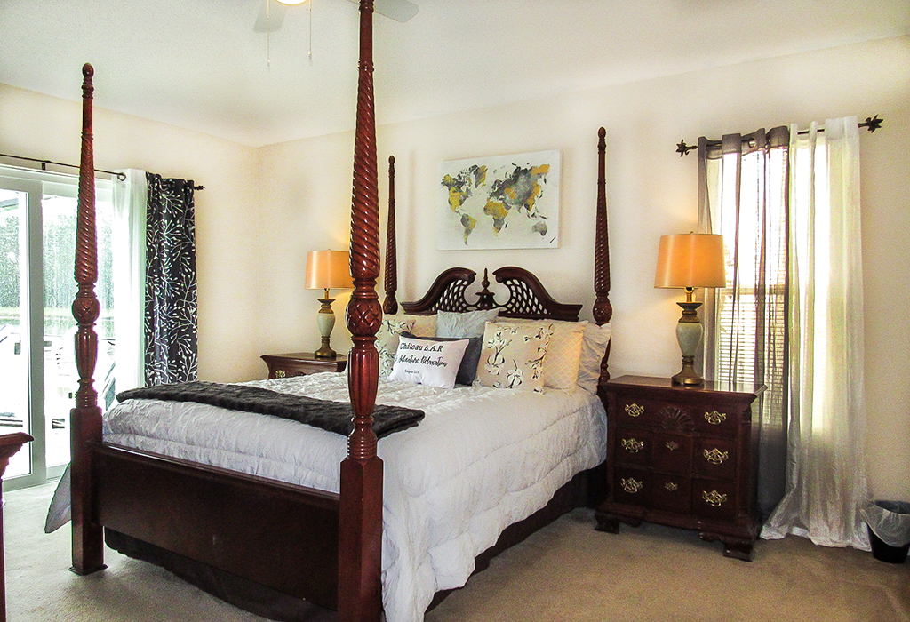 Master bedroom with comfortable queen size bed and convenient pool access.