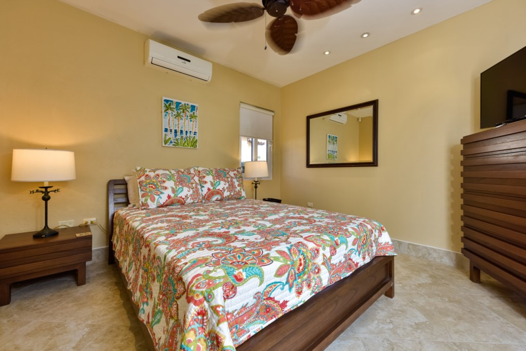 This bedroom with queen size bed, TV and air conditioning features also a shared walk-in closet.