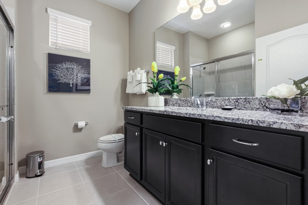 Classic single sink vanity with sliding glass shower and toilet