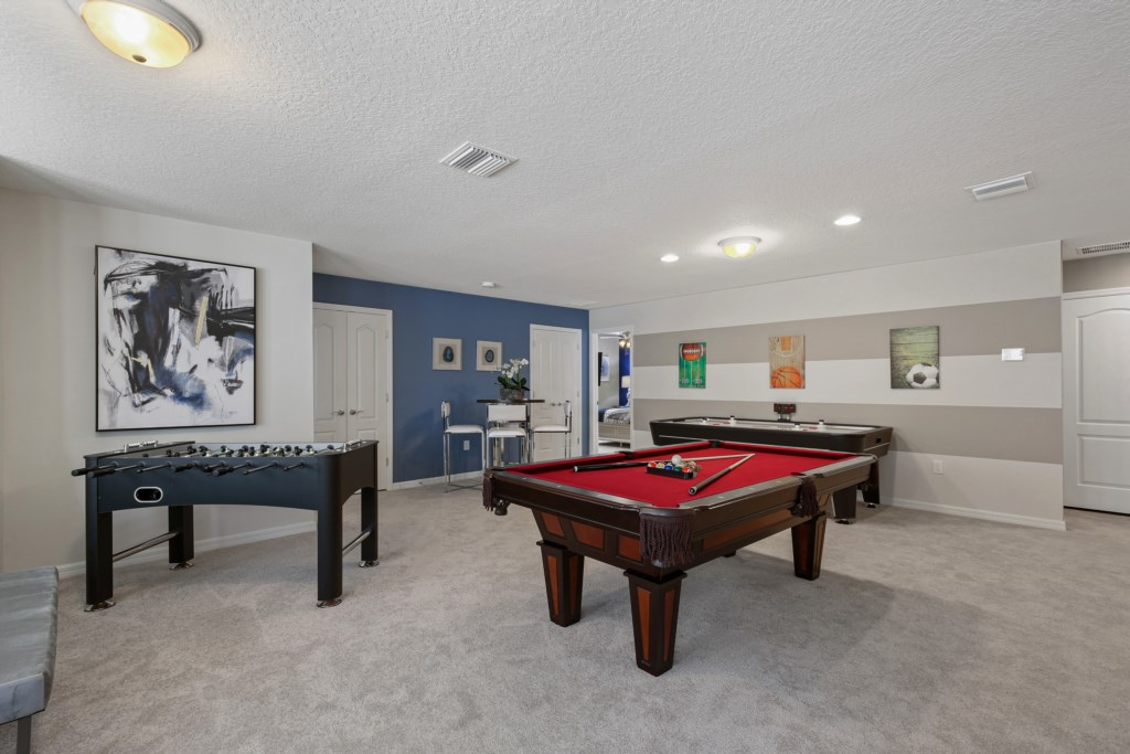 View 2 of fun play and lounge area including air hockey, pool and foosball tables