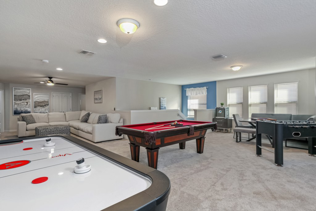 Fun play and lounge area including air hockey, foosball, pool table and comfy seating