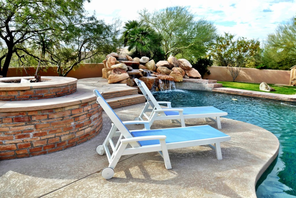 Backyard perfect for entertaining with lounge seats, pool and fire pit
