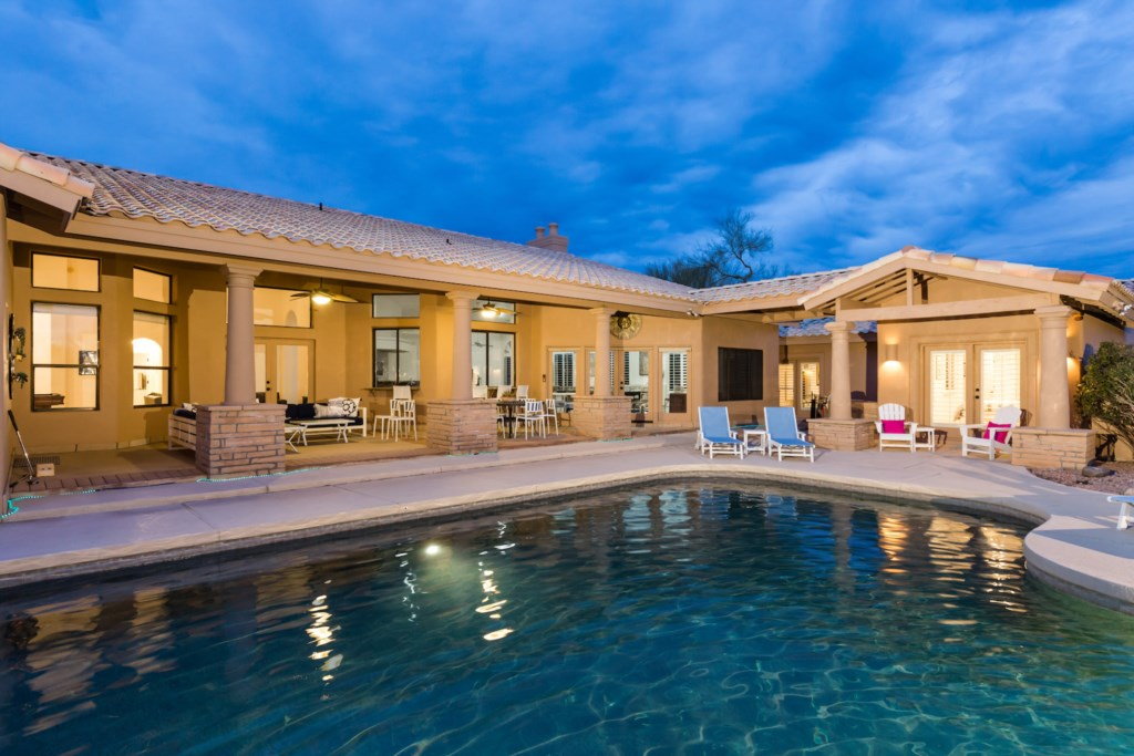 Incredible backyard with pool, putting green, lounge chairs and outdoor dining