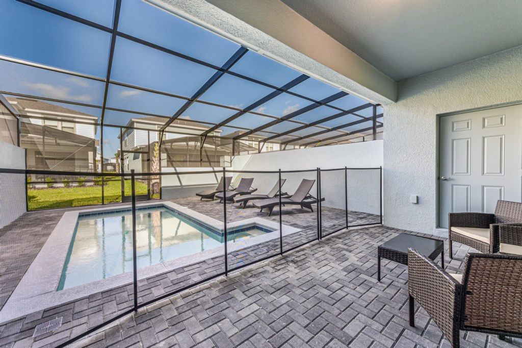 Gorgeous patio with loungers, pool, and pool safety fence