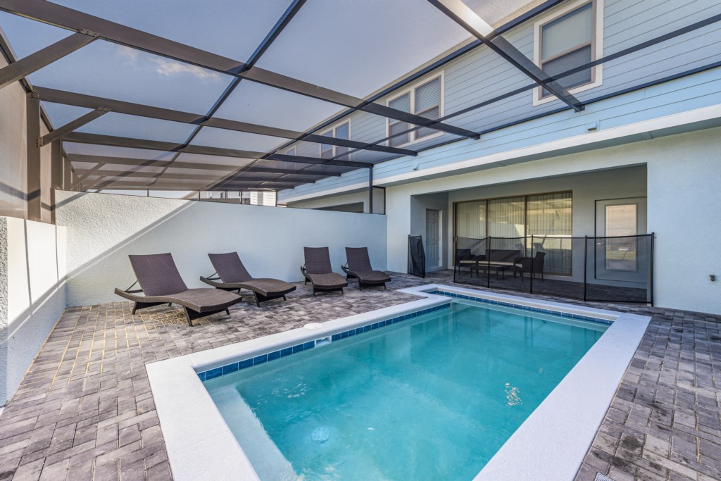 Luxurious pool with loungers and pool safety fence