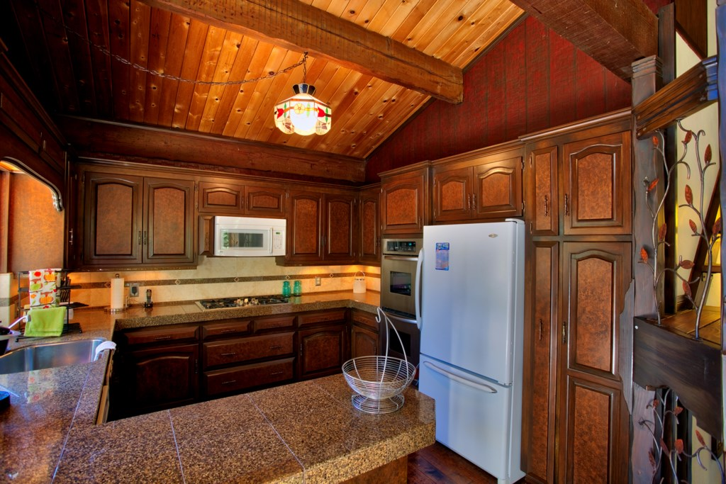Well-Stoked Kitchen with Granite Counters and Wood Cabinets