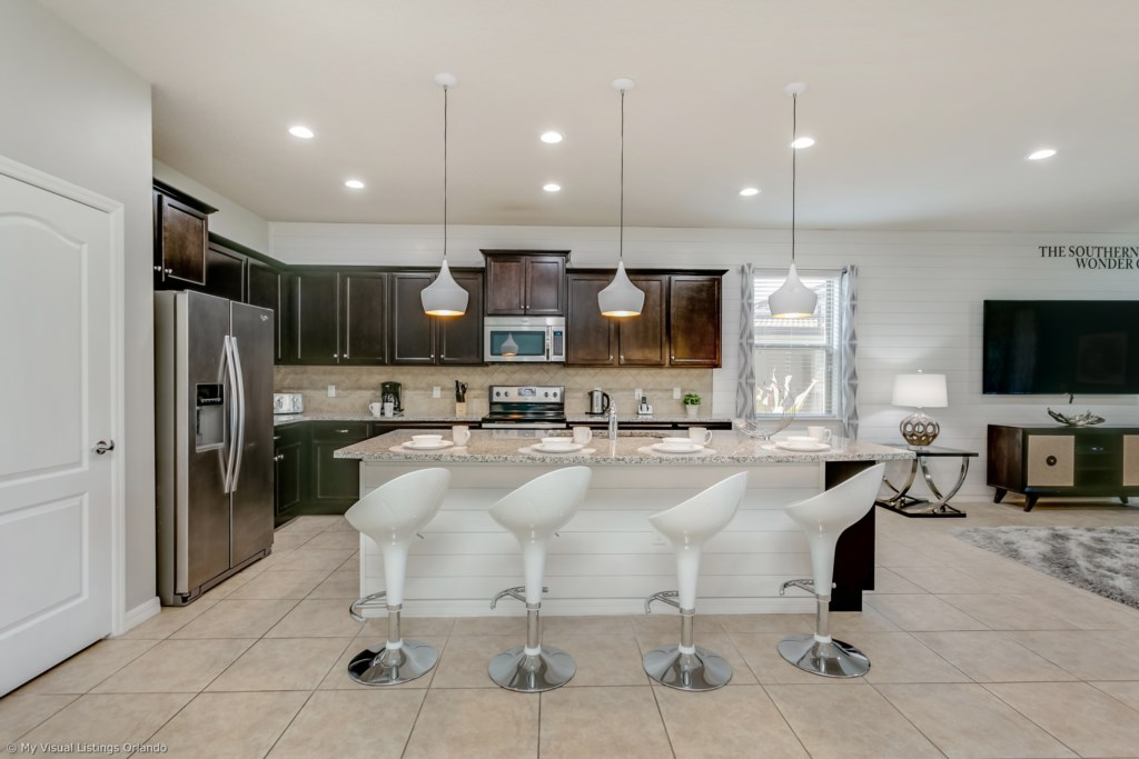 Modern style kitchen including microwave, stove, double door refrigerator and bar stool seating