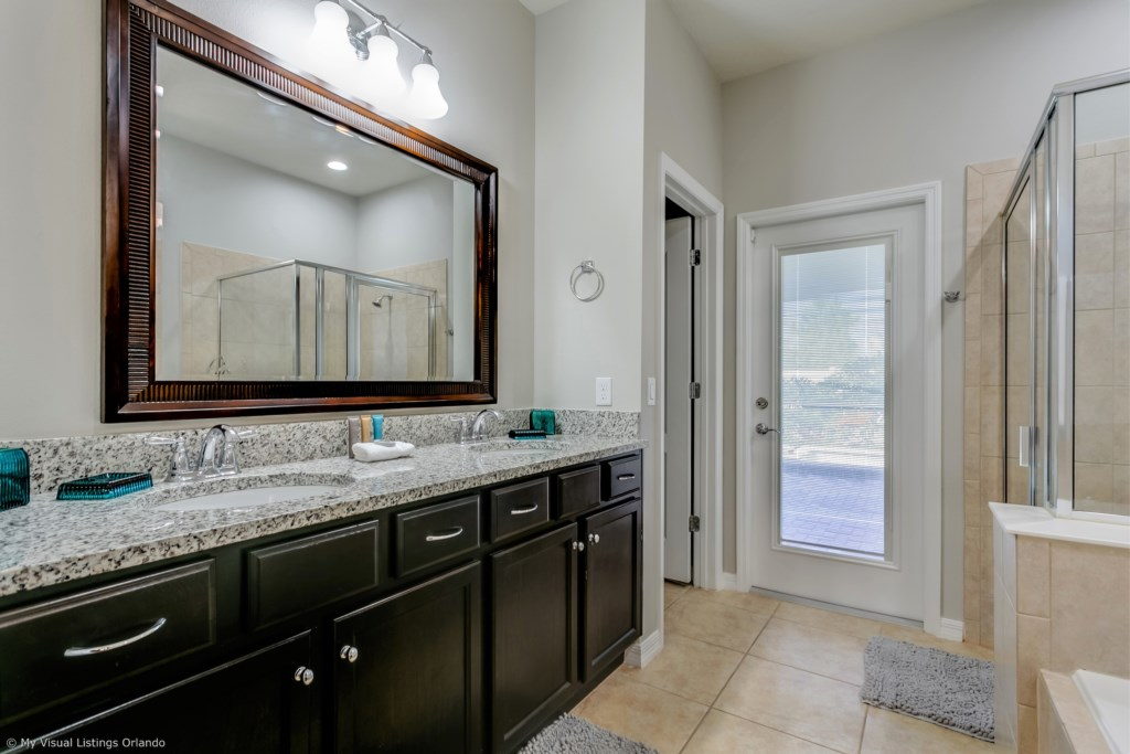 Lavish master bathroom with double sink vanity, glass shower, toilet, and access to back patio