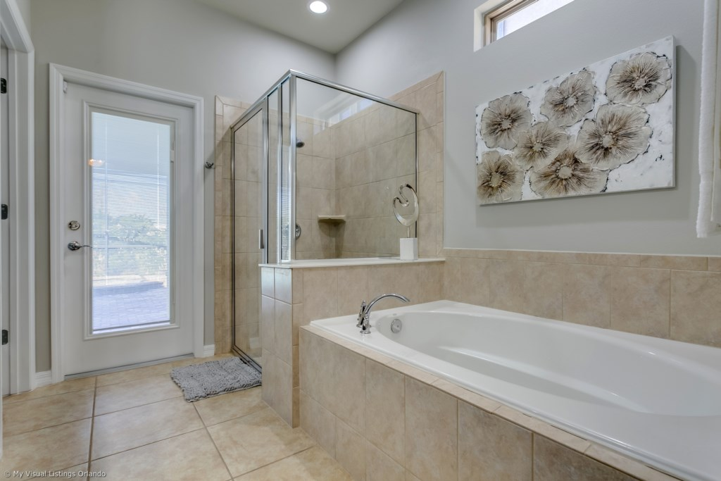 View 2 of lavish master bathroom with bath tub, glass shower, and access to back patio