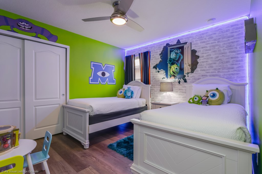 Awesome Monsters, Inc. themed room with two twin size beds, play table, and flat screen TV