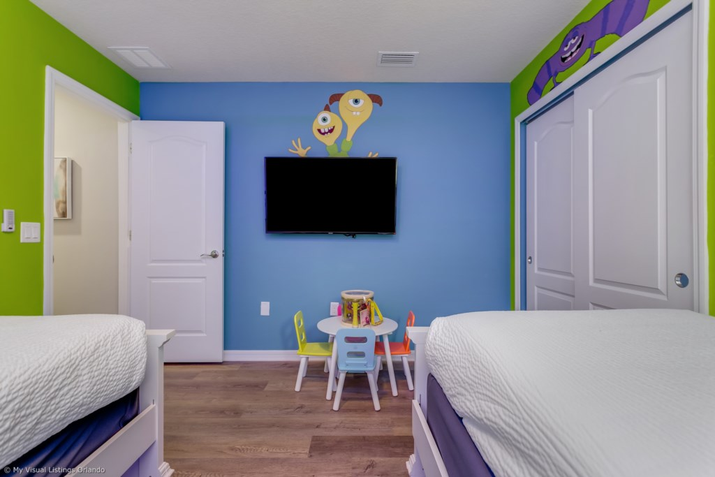 View 2 of awesome Monsters, Inc. themed room with two twin size beds, play table, and flat screen TV