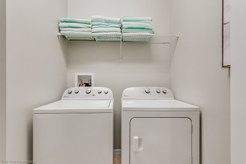 Convenient laundry room with full size washer and dryer with towels