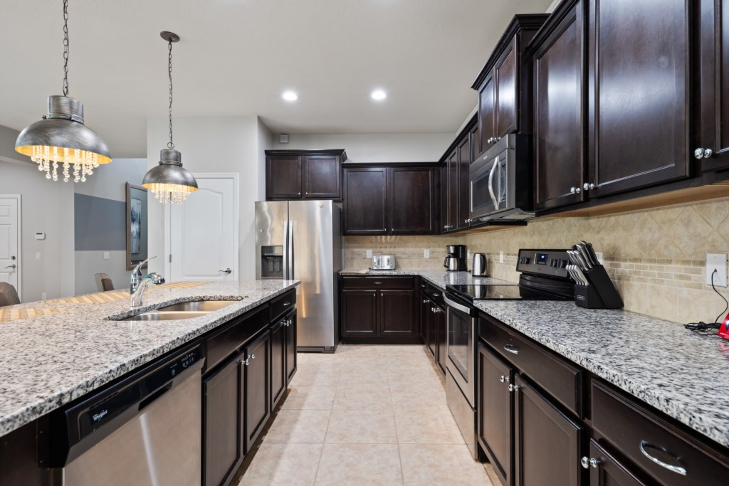Elegant kitchen area with oven, microwave, refrigerator and dish washer