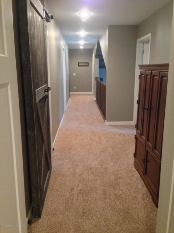 The upper level open walkway overlooks the family room with it's beautiful vaulted ceilings and soar