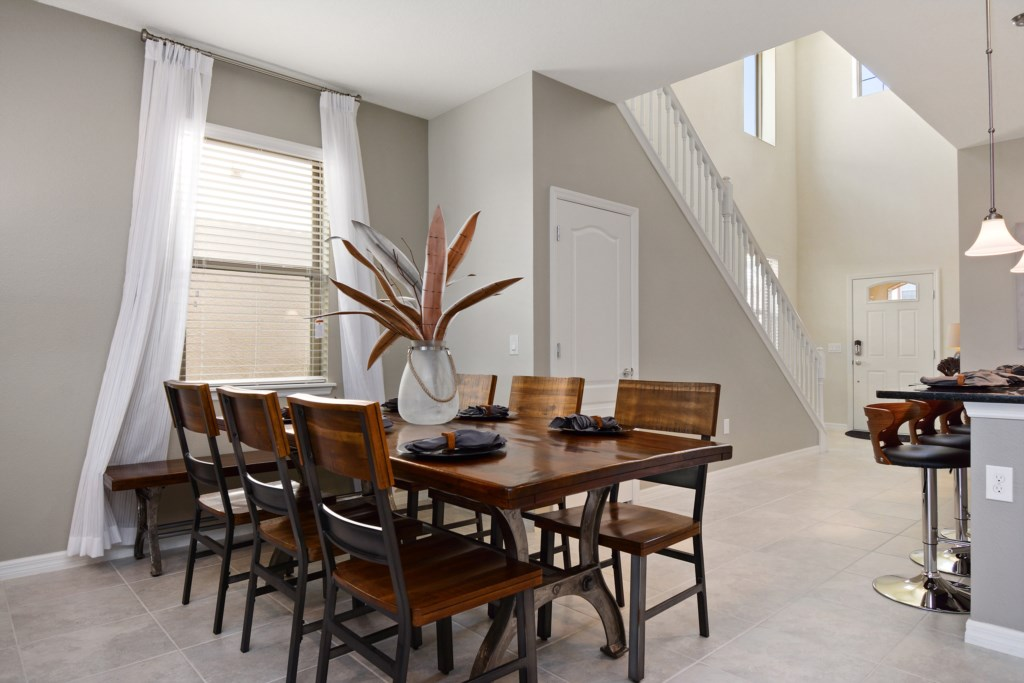 View 2 of elegant dining room table with front entrance and staircase