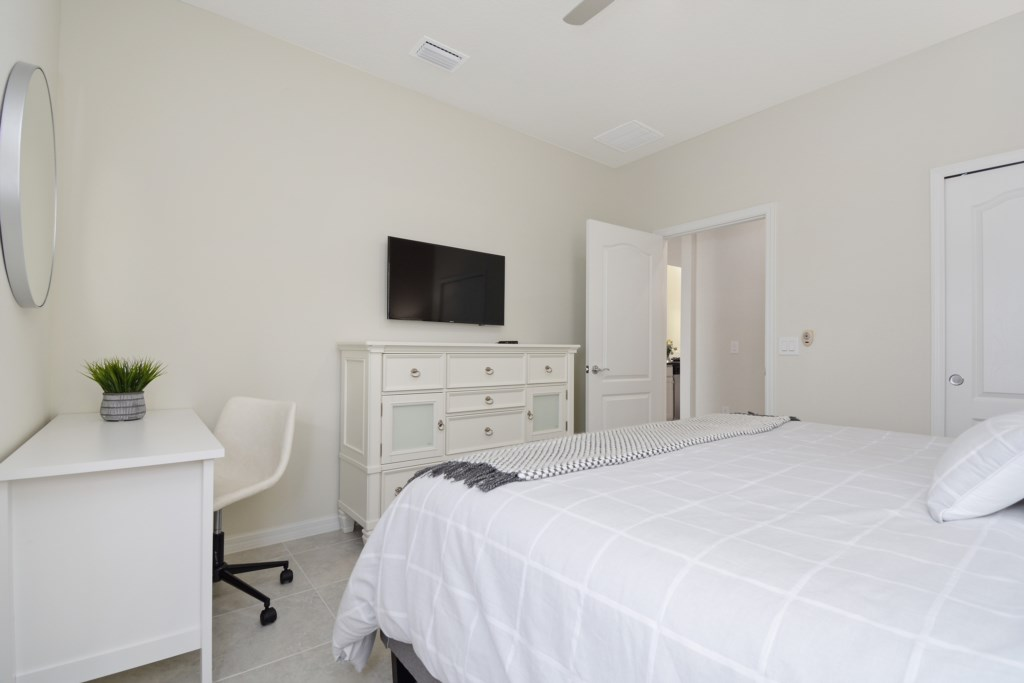 View 2 of gorgeous king size bed with table, chair, and access to glass walk in shower