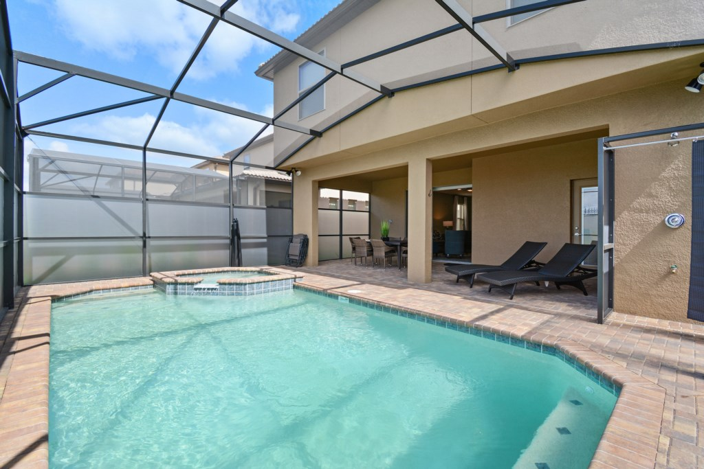 View 2 of grand pool and spa with comfortable patio furniture