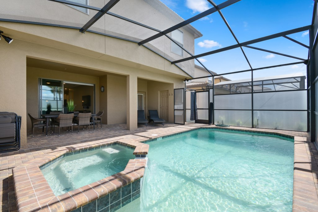 Grand pool and spa with comfortable patio furniture