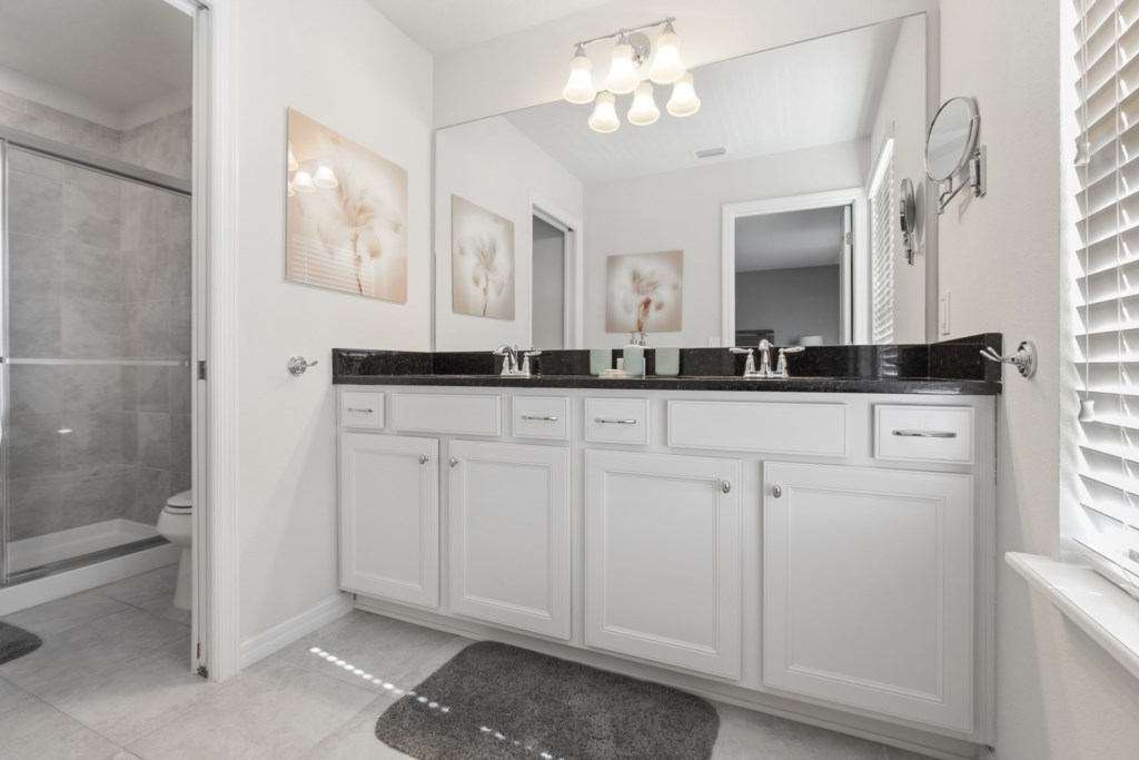 Classic double sink vanity with glass shower and toilet