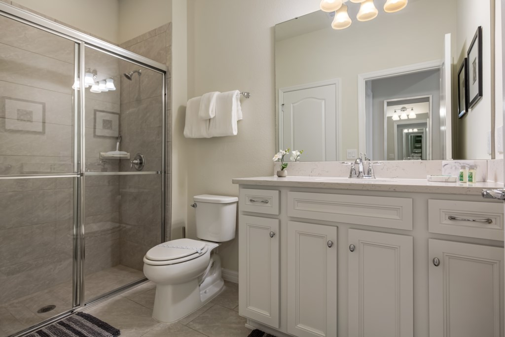 Fantastic single sink vanity with sliding glass shower and toilet