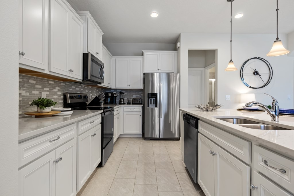 Grand kitchen area including microwave, stove, oven, dish washer, and double door refrigerator