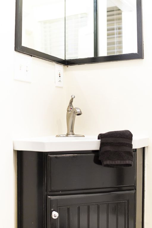Corner sink with large mirror in black and white bathroom