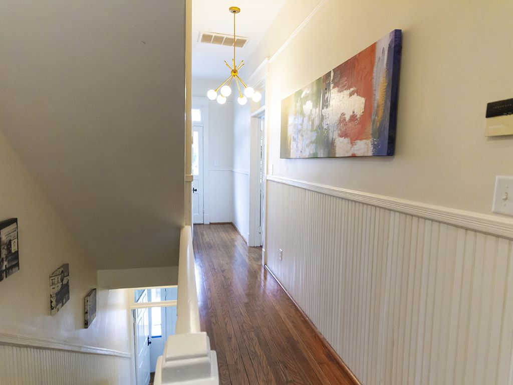 Hall leading to front porch. Hardwood floors throughout. Period wainscoting.