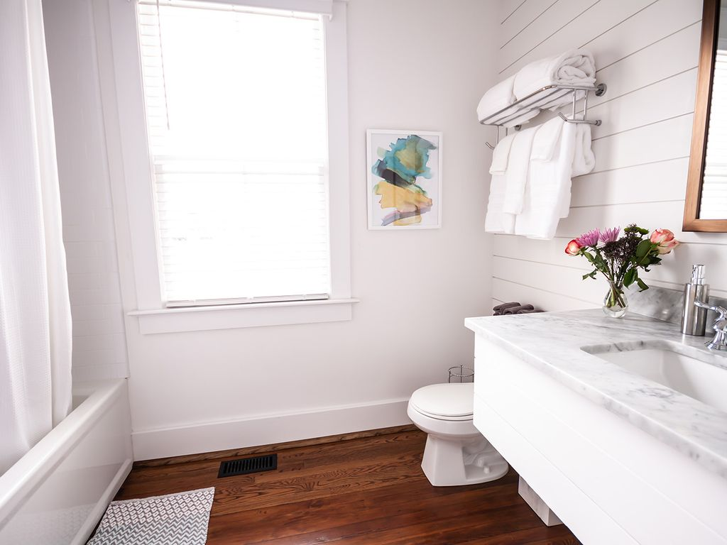 Large bathroom with soaking tub, shower, marble counter and hardwood floors