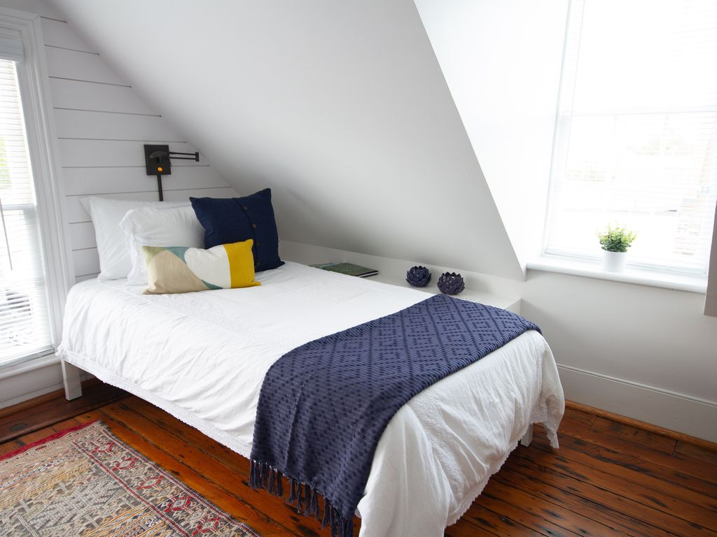 East dormer room with charging station book shelf running alongside bed.