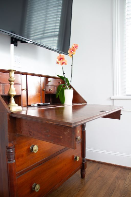 Antique desk. Appealing mix of old and new. (Remote controls for hvac & smart tv