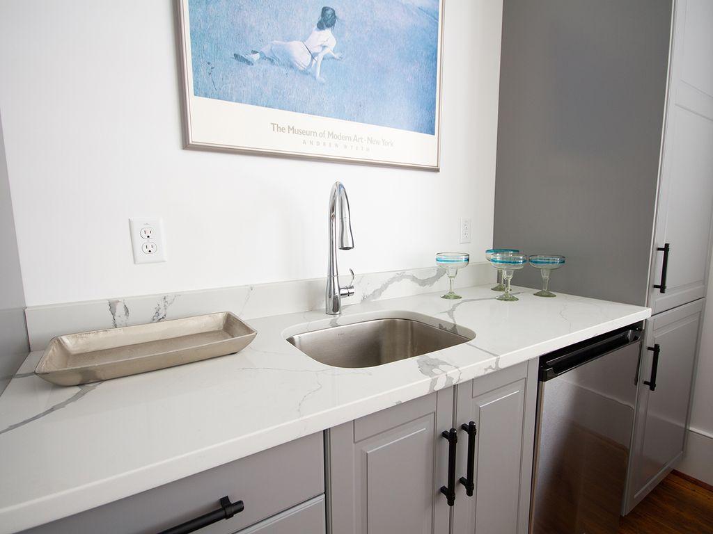Bar-sink in kitchenette. Microwave and under counter refrigerator + storage.