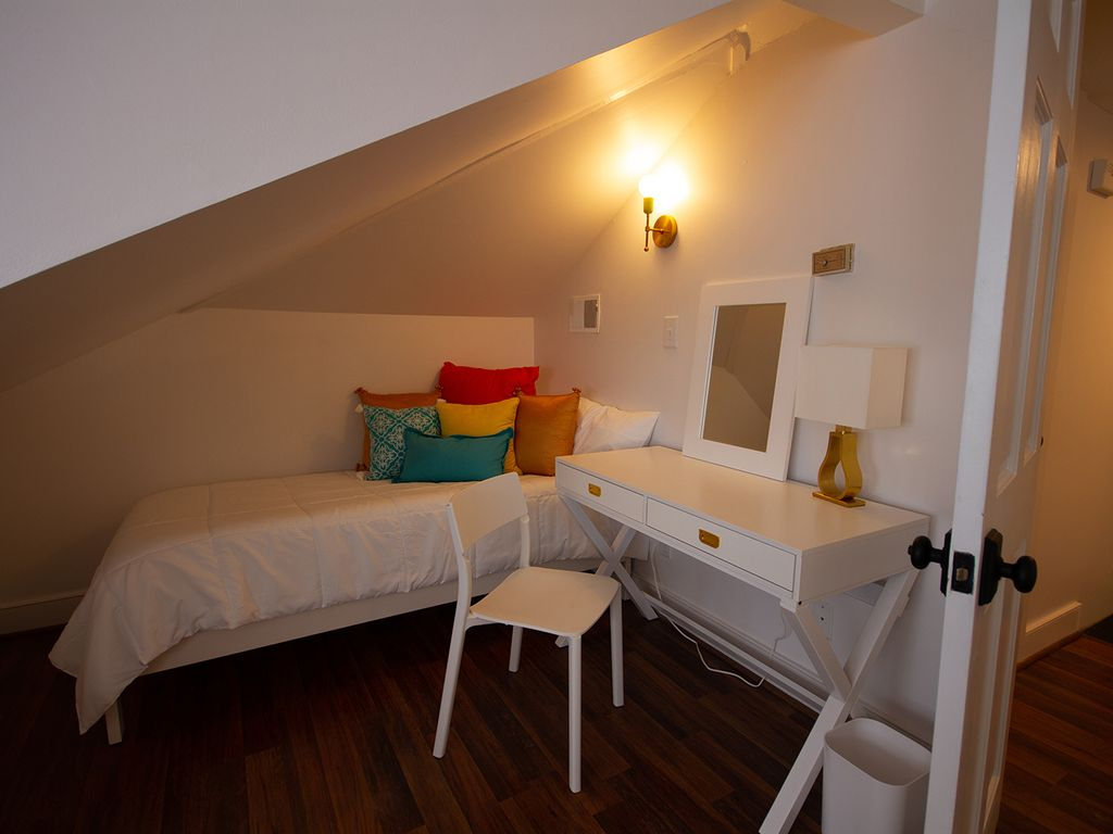 Twin bed in loft with writing desk/dressing table.