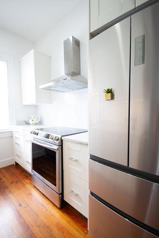 Ceramic cooktop, stylish vent, bright window, attractive refrigerator.