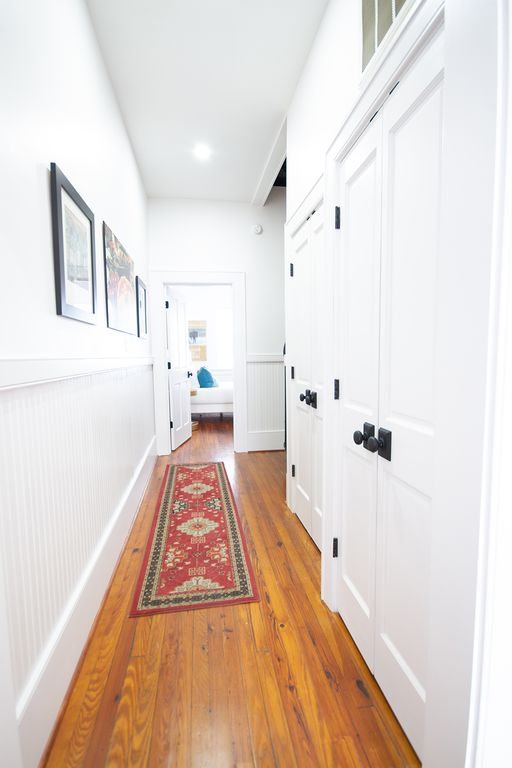 Center hall leading to middle bedroom. Laundry machines  behind door.