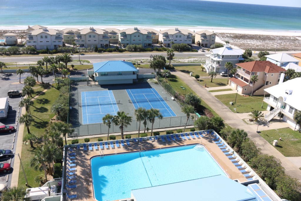 View of tennis courts and pool from balcony.