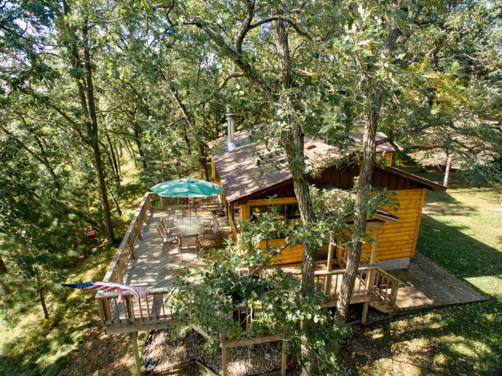 The cabin is set up into the trees with an elevated, yet close up view of the lake.