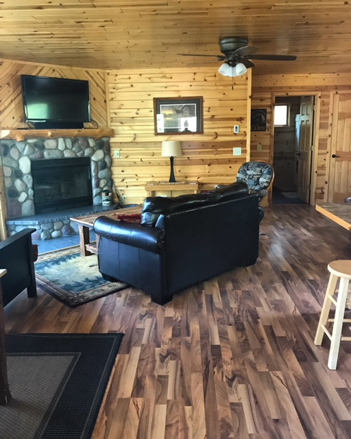 This cabin interior is knotty pine with a stone wood-burning fireplace.
