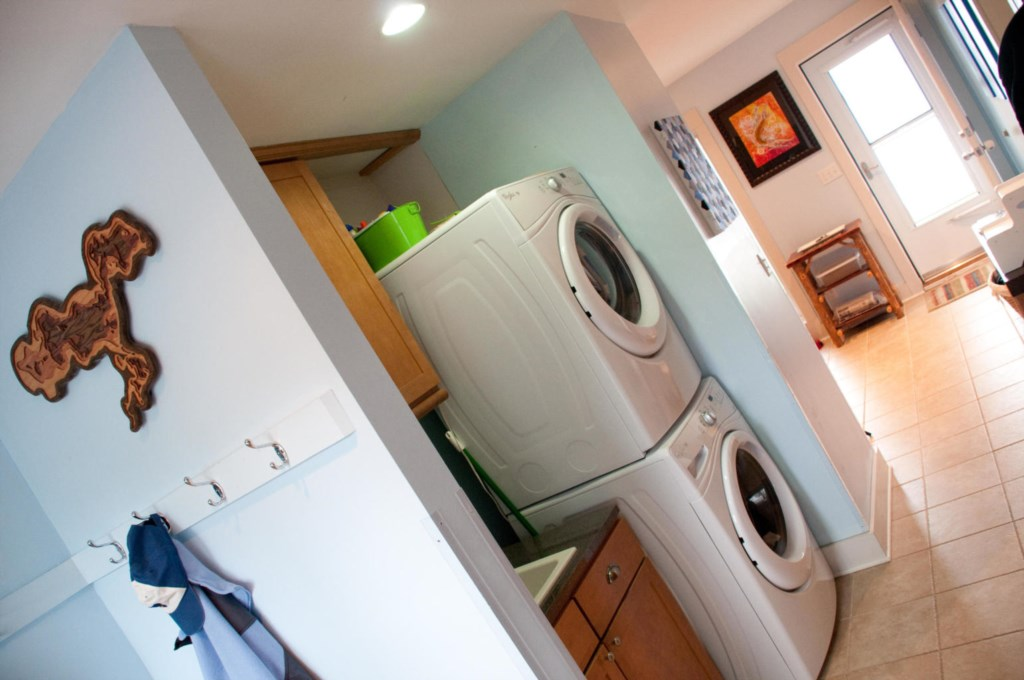 Stackable washer/dryer in laundry room.