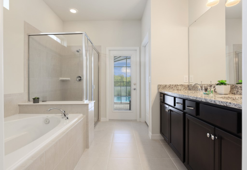 Elegant bathroom inlcuding bathtub, shower, double sink vanity, and access to patio