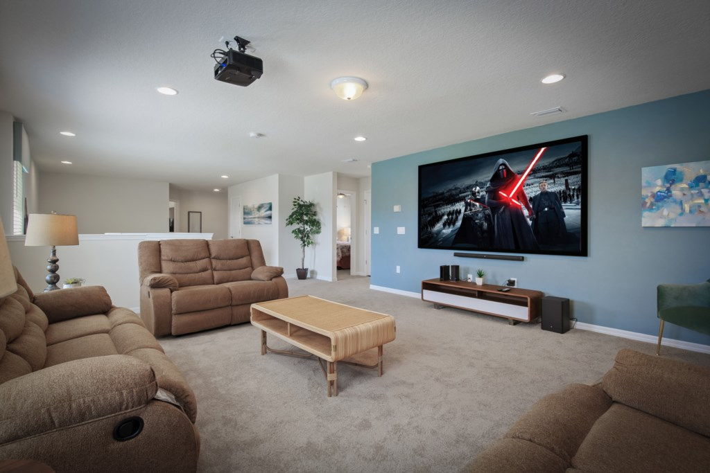 Upstairs entertainment projection movie room with cozy reclining chairs