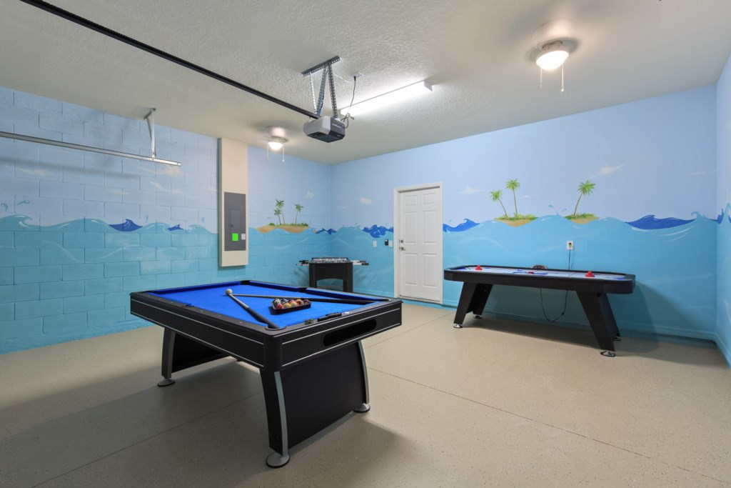 Garage entertainment center with pool table, air hockey, and foosball