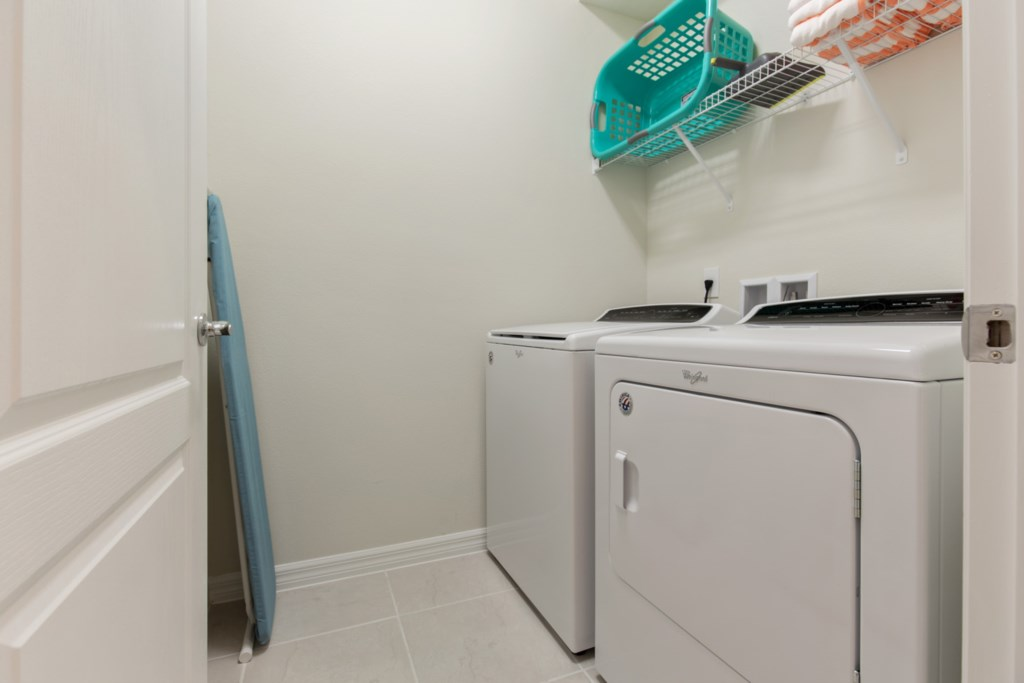 Laundry room with full size washer and dryer, laundry basket, ironing board, and dust pan set