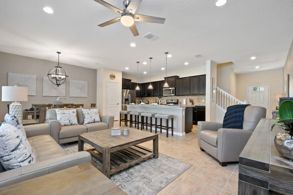 Stunning living room area with modern style kitchen and barstool seating