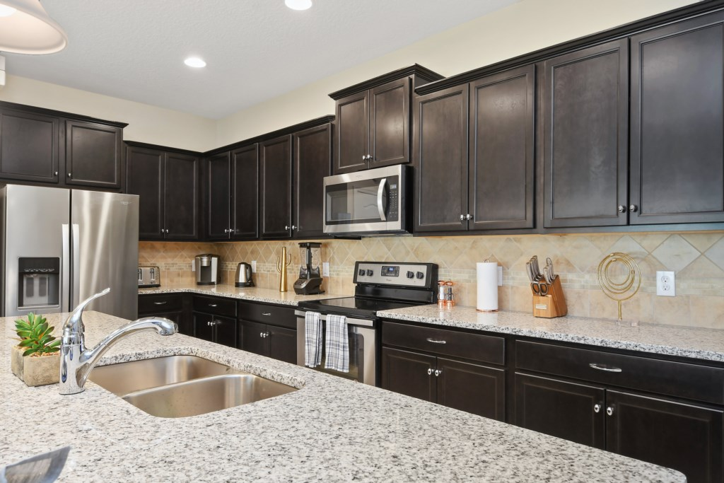View 2 of stunning modern style kitchen with microwave, stove, oven, and double door refrigerator