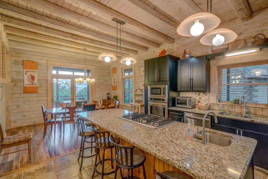 Another view of kitchen and dining area that leads to screened in porch