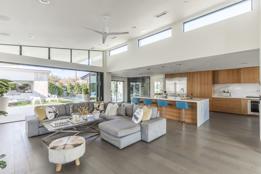Large open concept living room with doors that completely open up to the backyard