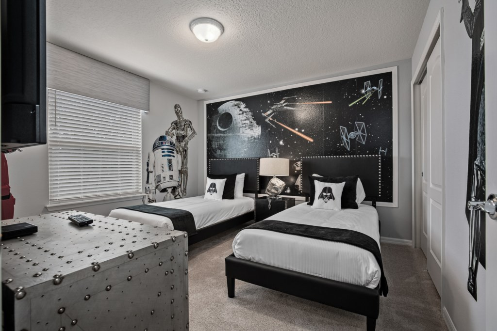 Star Wars themed bedroom with two twin beds and flat screen TV