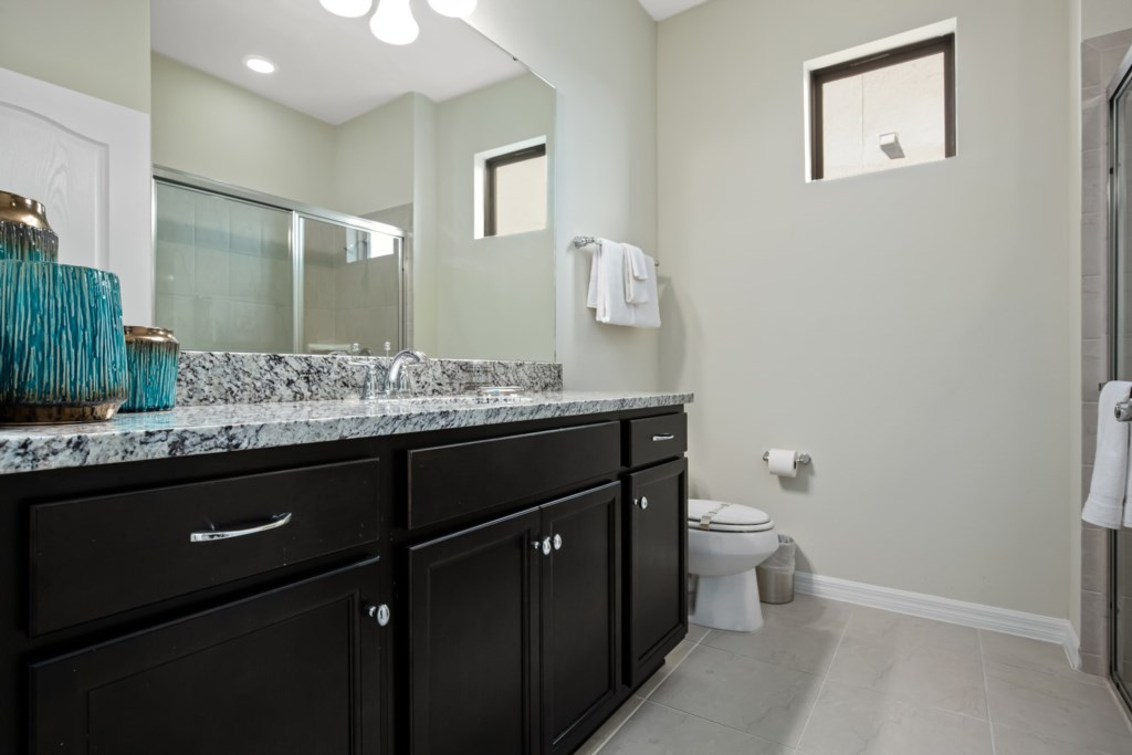 Modern single sink vanity, toilet, and glass shower