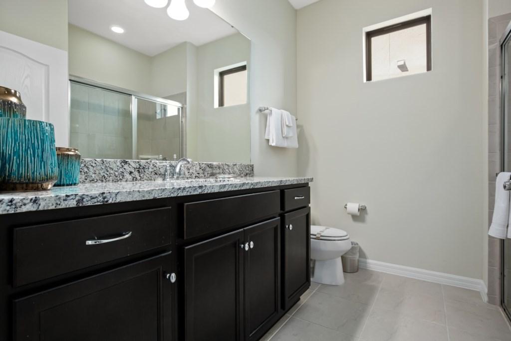 Modern single sink vanity, toilet, and glass shower